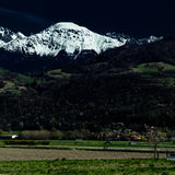 White mountain. Dramatic photograph with dark sky and environment contrasting with the white snowy peak of a mountain Stock Photos