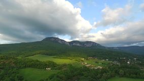 White Mountains With Trees On Hills. Aerial view of the small white mountain with forest on the slopes and small village stock footage