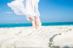 White moving skirt  and feet in sand on the Royalty Free Stock Photography