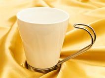 White mug. Photo of single white mug at the golden fabric drapery Royalty Free Stock Photo