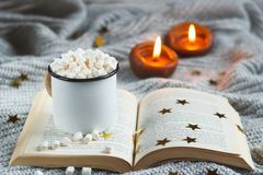 White mug with cocoa and marshmallow on an open book on a light gray textured bac stock photo