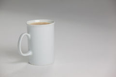 White mug of coffee with creamy froth. On white background royalty free stock photo