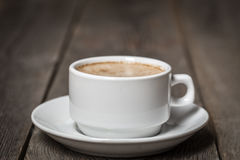 White mug with coffee standing on wooden table. Royalty Free Stock Photos