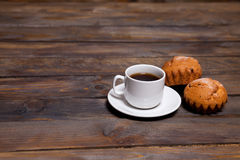White mug of coffee and two cupcakes on wooden background Royalty Free Stock Photos