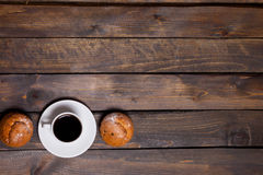 White mug of coffee and two cupcakes on wooden background Stock Photo