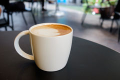 White mug cup containing hot cappuccino coffee Royalty Free Stock Photography