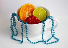 The white mug with cut mandarin, lime, pomegranate and blue beads royalty free stock photo