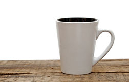 White mug empty blank for coffee. On a wooden table over white background Royalty Free Stock Photos