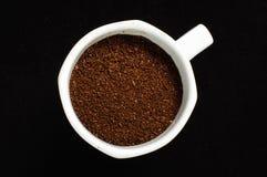 White mug full of ground coffee coffee addiction concept Stock Photo