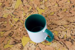 White mug with a green handle stock photography