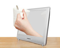 White mug in hand leans out TV screen Royalty Free Stock Photos