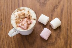 Hot drink with marshmallows on a wooden background Royalty Free Stock Images
