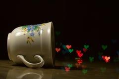 White mug and love hearts bokeh. White mug on the table, love hearts bokeh stock images