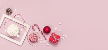 White mug with marshmallows Candy Cane gifts boxes red ball packaging lace photo frame on pink background top view Flat Lay. Winter traditional drink food stock photography