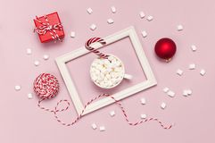 White mug with marshmallows Candy Cane gifts boxes red ball packaging lace photo frame on pink background top view Flat Lay. stock photos