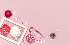 White mug with marshmallows Candy Cane gifts boxes red ball packaging lace photo frame on pink background top view Flat Lay Winter. Traditional drink food royalty free stock photo
