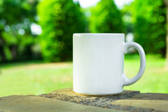 White mug, mock up, empty space for artwork, text, standing on stone, outdoors, green grass, trees, sky in the background Stock Image