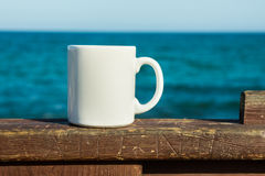 White mug, mock up, empty space for artwork, text, standing on wood plank, turquoise sea, clear blue sky Stock Images