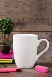 White mug mockup. Blank mug. Coffee mug mockup with bright neon colors pencils and notebooks. Potted plant bonsai behind Stock Photo