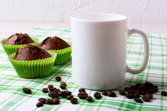 White mug mockup with chocolate muffins on green checkered napki Royalty Free Stock Image