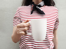 White mug mockup. Close up of a young woman wearing a striped t-shirt and scarf and holding cup of tea or coffee. Feminine stock photography. Front view Stock Images