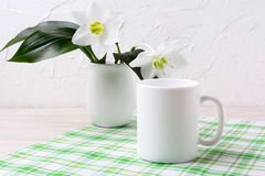 White mug mockup with lily in vase on green checkered napkin Royalty Free Stock Images