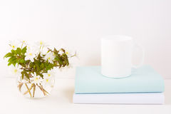 White mug mockup with Rue Anemone flowers Royalty Free Stock Image