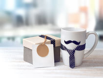 White mug mustache gift box fathers day concept. White mug on wooden table with mustache, tie, gift, empty card for text.Fathers day concept background Stock Photography