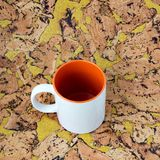 White mug with a orange handle. White mug with a orangehandle on a background of a textured cork Royalty Free Stock Image