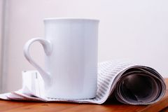 White mug over newspaper Stock Photos