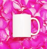 White mug on petals of pink roses background Stock Image