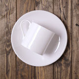 White mug and plate. Coffee cup and saucer on a wooden background Royalty Free Stock Photo