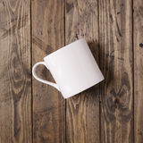 White mug and plate. White coffee cup on a wooden background Royalty Free Stock Photo