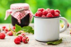 White mug of raspberries and jar of berry jam on background. Outdoors Stock Photo