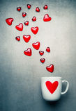 White mug with red heart and flying glass hearts . Love symbols and Valentines day concept Royalty Free Stock Photography
