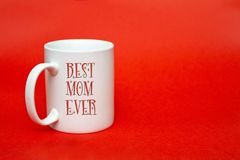 """White mug with sign """" Best mom ever"""" on red background. Copy space for writing. White glass isolated. women's day. White mug with sign """" Best Royalty Free Stock Photography"""