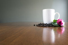 White Mug with spilled Coffee Beans and Pink Rose stock image