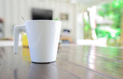 White mug with spoon on the table Stock Photos