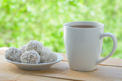 White mug with tea and gingerbread cookies on wooden table by the open window. stock image