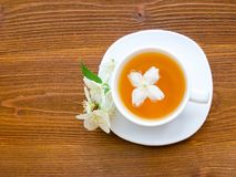 White mug of tea with jasmine on a brown wooden table. Close up, top view Stock Image