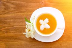 White mug of tea with jasmine on a brown wooden table. Close up,. Top view Royalty Free Stock Image