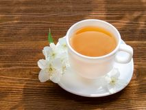 White mug of tea with jasmine on a wooden table. Close up, top view Royalty Free Stock Photos