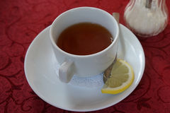White mug of tea on a red tablecloth. Spring tree against the background of the city and Bay Stock Image