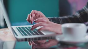White mug with tea on the table near laptop. Close-up of female hands typing on a laptop keyboard. Female hand with bracelet printed on the keyboard. An unknown stock video footage