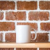 White mug on vintage brick wall background. Wooden display shelf for showing drink cup in grunge concept. Brickwork surface and stock photo