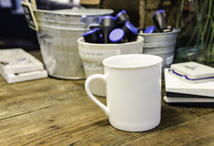 White mug on wooden table. White mug with black coffee on wooden table Royalty Free Stock Images