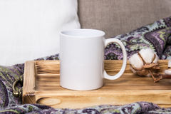 White mug on a wooden tray, the Mockup. Cozy home, linen and wool decorations.  Stock Images