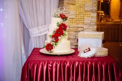 White multilevel wedding cake decorated with red cream flowers on table. Candy bar concept