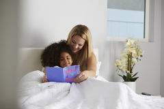 White mum and black daughter looking at card, full length Stock Images