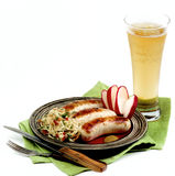 White Munich Sausages and Beer. Delicious Grilled White Munich Sausages with Pickled Cabbage, Chopped Radish and Glass of Beer on Green Napkin isolated on White royalty free stock image